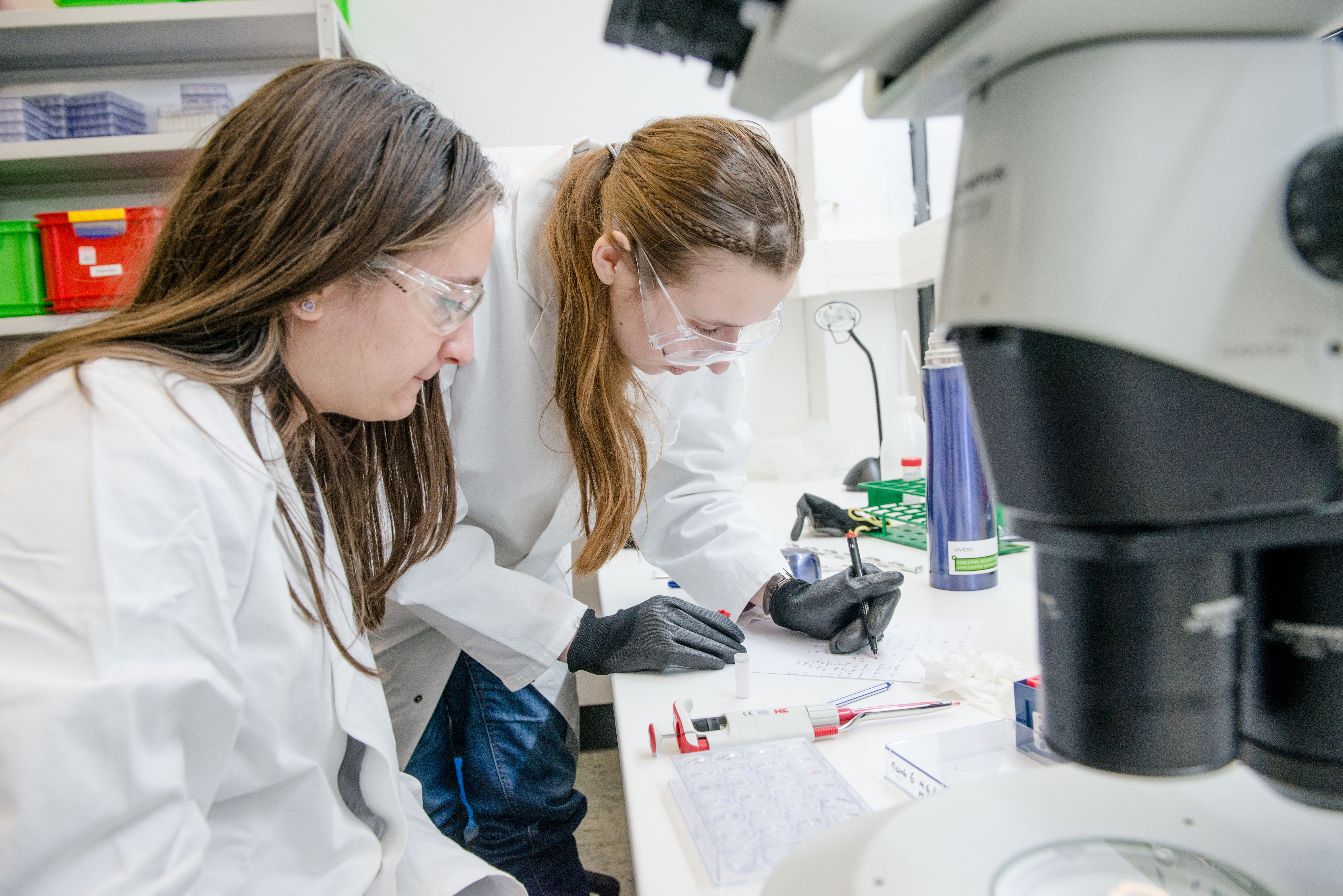 Two female reserchers analyse a sample