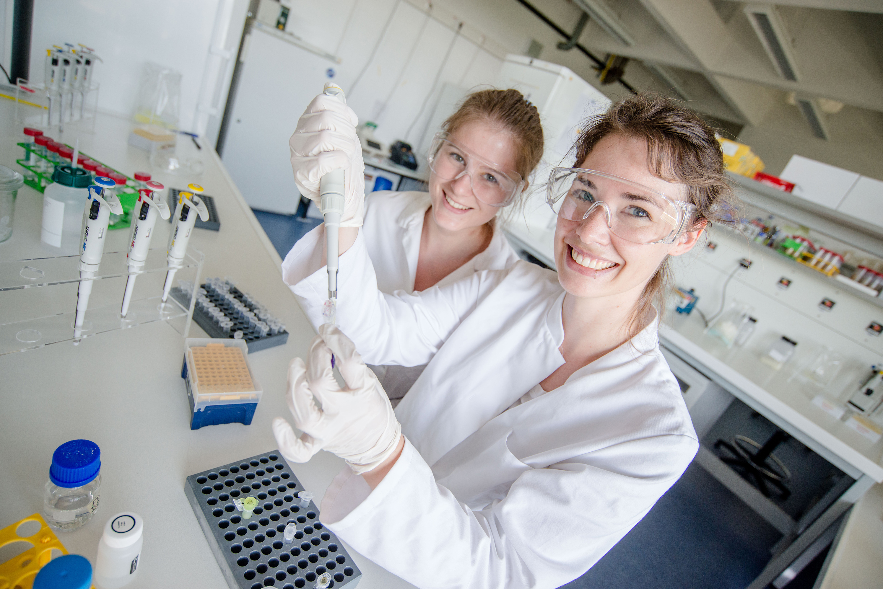 Two young female researchers in white coats in the laboratory